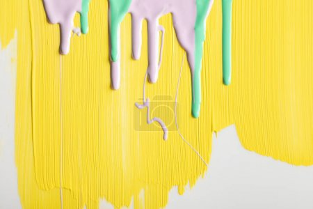 Foto de Pintado de fondo amarillo con pinturas verdes y púrpuras que fluyen - Imagen libre de derechos