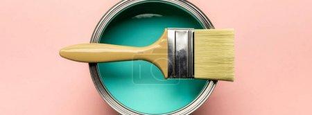 Photo pour Coup panoramique de boîte avec la peinture verte et le pinceau sur la surface rose - image libre de droit