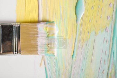 Photo pour Vue du haut de la brosse et des coups de pinceau colorés sur la surface blanche - image libre de droit