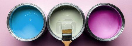 plano panorámico de pincel y latas con pinturas sobre superficie rosa