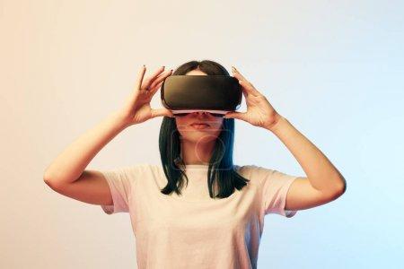 morena mujer joven tocando auriculares de realidad virtual en beige y azul
