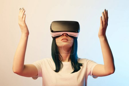Photo for Attractive young woman gesturing while wearing virtual reality headset on beige and blue - Royalty Free Image