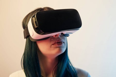 Photo for Brunette woman wearing virtual reality headset on beige - Royalty Free Image