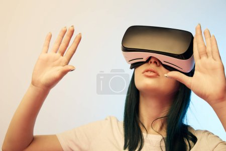 Photo for Brunette girl wearing virtual reality headset and gesturing on beige and blue - Royalty Free Image