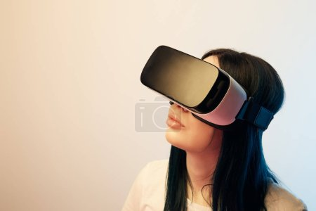 Photo for Brunette girl wearing virtual reality headset on beige and blue - Royalty Free Image