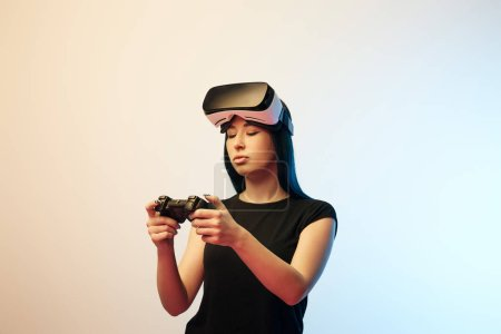 Photo for KYIV, UKRAINE - APRIL 5, 2019: Young woman looking at joystick while wearing virtual reality headset on beige and blue - Royalty Free Image