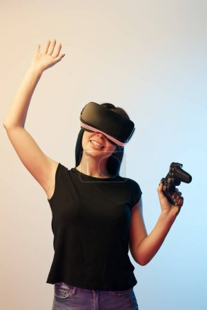Photo for KYIV, UKRAINE - APRIL 5, 2019: Cheerful woman holding joystick while wearing virtual reality headset and waving hand on beige and blue - Royalty Free Image