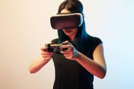 Photo pour Kiev, Ukraine - 5 avril 2019: Une jeune femme jouant à un jeu vidéo tout en portant un casque de réalité virtuelle sur beige et bleu - image libre de droit