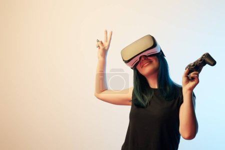 Photo pour KYIV, UKRAINE - APRIL 5, 2019: Cheerful brunette woman holding joystick while showing peace sign and wearing virtual reality headset on beige and blue - image libre de droit
