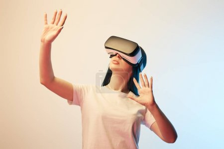 Photo for Young woman in virtual reality headset gesturing on beige and blue - Royalty Free Image