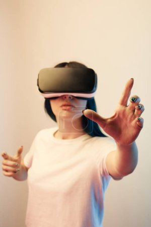 Photo for Selective focus of brunette young woman in virtual reality headset gesturing on beige - Royalty Free Image