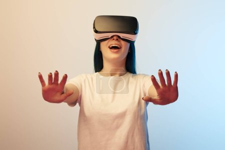 selective focus of cheerful woman in virtual reality headset gesturing on beige and blue