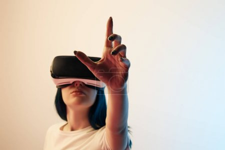 Photo for Selective focus of brunette girl wearing virtual reality headset and gesturing on beige and blue - Royalty Free Image