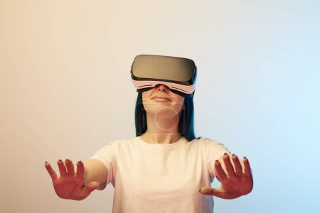 Photo for Selective focus of happy young  woman in virtual reality headset gesturing on beige and blue - Royalty Free Image