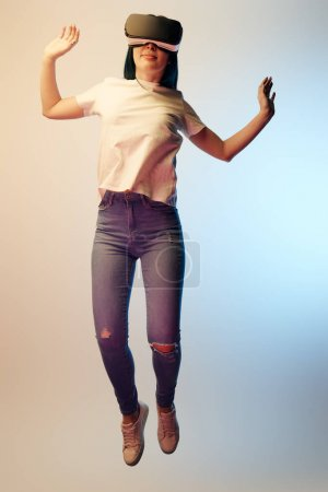 Photo for Cheerful woman in virtual reality headset levitating and gesturing on beige and blue - Royalty Free Image