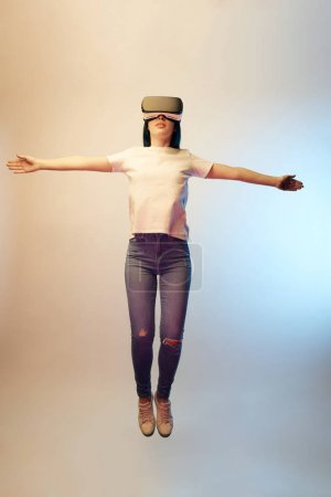 Photo for Young woman in virtual reality headset with outstretched hands levitating on beige and blue - Royalty Free Image