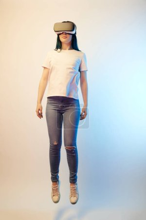 Photo for Young woman in virtual reality headset levitating on beige and blue - Royalty Free Image