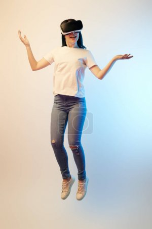 Photo for Happy brunette woman in virtual reality headset levitating and showing shrug gesture on beige and blue - Royalty Free Image