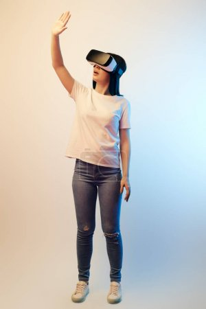 Photo for Brunette young woman in virtual reality headset standing and gesturing on beige and blue - Royalty Free Image