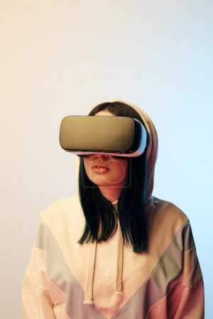 Photo for Beautiful brunette woman in virtual reality headset on beige and blue - Royalty Free Image