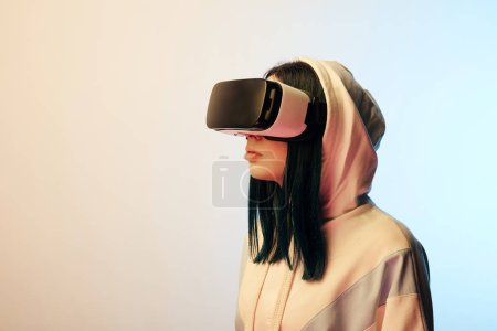 Photo for Beautiful brunette young woman in virtual reality headset on beige and blue - Royalty Free Image