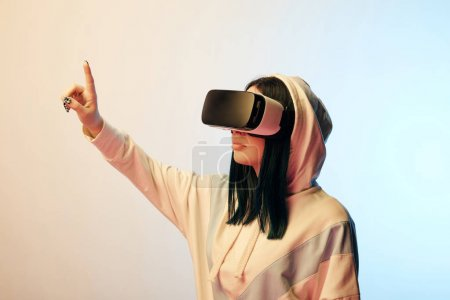 Photo for Beautiful brunette woman in virtual reality headset pointing with finger on beige and blue - Royalty Free Image