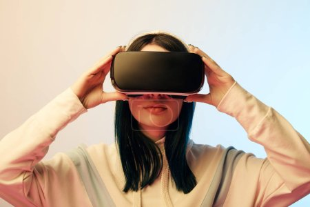 Photo for Beautiful brunette young woman touching virtual reality headset on beige and blue - Royalty Free Image