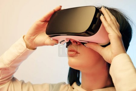 Photo for Close up of beautiful brunette woman touching virtual reality headset on beige and blue - Royalty Free Image