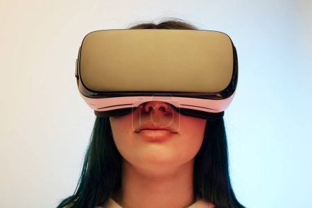 Photo for Low angle view of brunette woman in virtual reality headset on beige and blue - Royalty Free Image