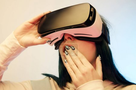Photo for Low angle view of surprised woman covering mouth while wearing virtual reality headset on beige and blue - Royalty Free Image