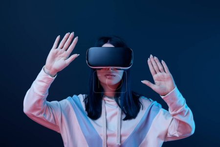 young brunette woman wearing virtual reality headset and gesturing on blue