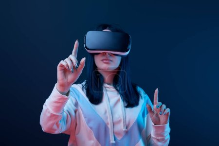 selective focus of young brunette woman wearing virtual reality headset and pointing with fingers on blue