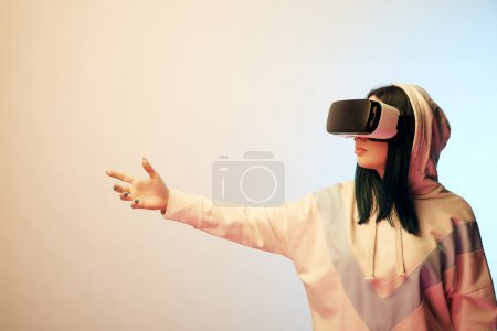 young brunette girl wearing virtual reality headset and gesturing on beige and blue
