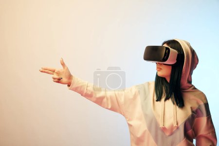 Photo for Brunette girl wearing virtual reality headset and gesturing on beige with gradient - Royalty Free Image