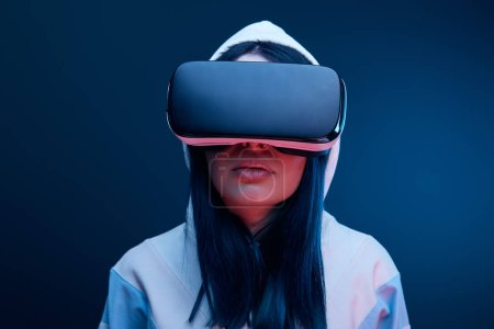 Photo for Brunette girl in hood wearing virtual reality headset on blue - Royalty Free Image