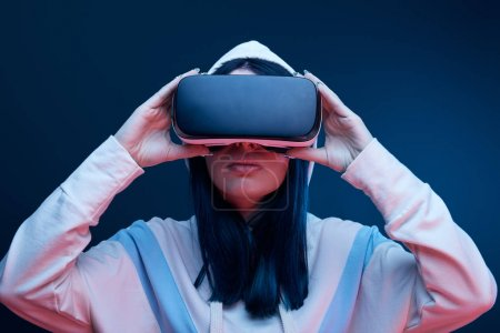 Photo for Brunette girl in hood touching virtual reality headset on blue - Royalty Free Image