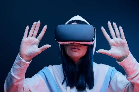 foyer sélectif de la fille brune dans le geste de capuche tandis que la réalité virtuelle casque sur bleu
