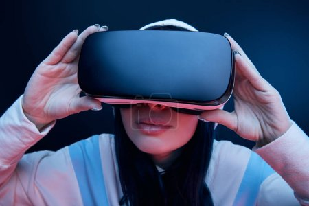 Photo for Selective focus of brunette woman in hood touching virtual reality headset on blue - Royalty Free Image