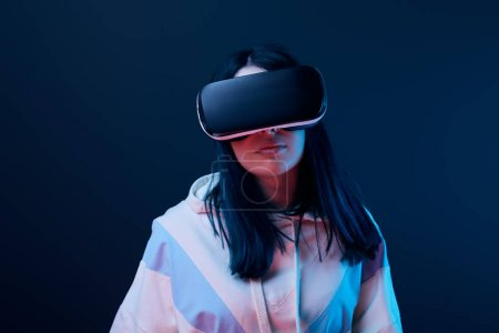 Photo for Brunette young woman using virtual reality headset on blue - Royalty Free Image