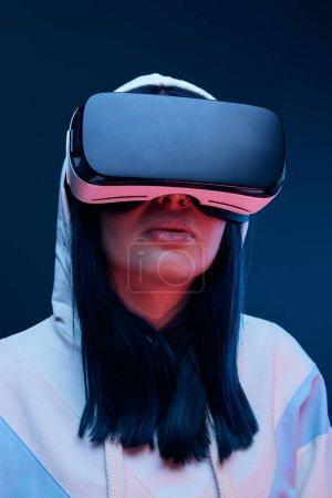 vue à faible angle de la jeune femme brune dans le capot en utilisant un casque de réalité virtuelle sur bleu