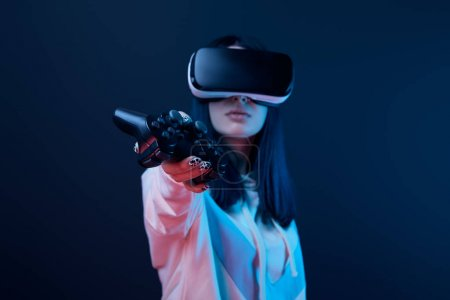 Photo for KYIV, UKRAINE - APRIL 5, 2019: Selective focus of young woman holding joystick while using virtual reality headset on blue - Royalty Free Image