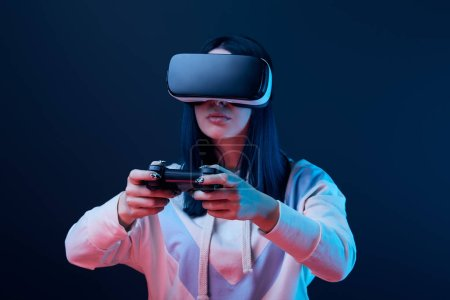 Photo for KYIV, UKRAINE - APRIL 5, 2019: Selective focus of young woman playing video game while wearing virtual reality headset on blue - Royalty Free Image