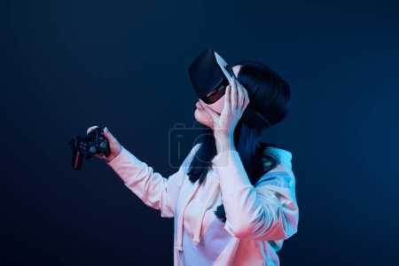 Photo for KYIV, UKRAINE - APRIL 5, 2019: Brunette woman holding joystick while touching virtual reality headset on blue - Royalty Free Image