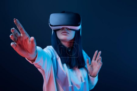 Photo for Selective focus of young woman gesturing while using virtual reality headset on blue - Royalty Free Image