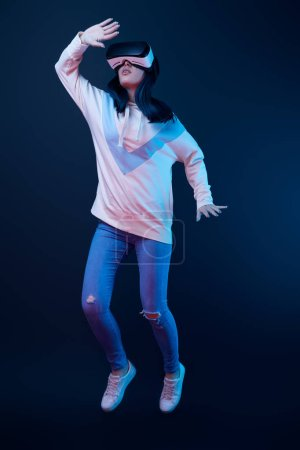 young woman gesturing while using virtual reality headset and jumping on blue