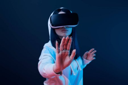 Photo for Selective focus of woman gesturing while using virtual reality headset on blue - Royalty Free Image