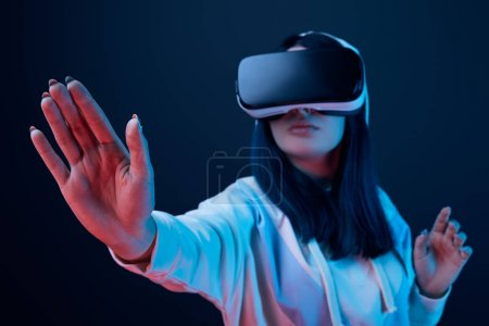 Photo for Selective focus of girl gesturing while using virtual reality headset on blue - Royalty Free Image
