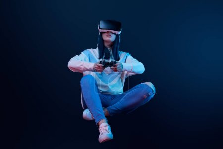 Photo for KYIV, UKRAINE - APRIL 5, 2019: Woman holding joystick while levitating, playing video game and wearing virtual reality headset on blue - Royalty Free Image
