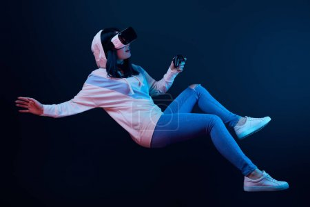 Photo for KYIV, UKRAINE - APRIL 5, 2019: Surprised woman in virtual reality headset levitating and holding joystick on blue - Royalty Free Image