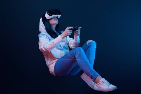 Foto de KYIV, UKRAINE - APRIL 5, 2019: Low angle view of young woman holding joystick while playing video game in virtual reality headset on blue - Imagen libre de derechos